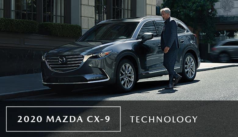 A man standing next to a 2020 Mazda CX-9 - Bert Ogden Mazda Edinburg in Edinburg, TX