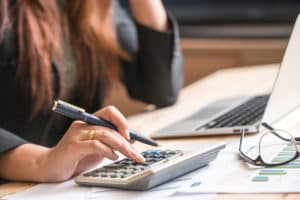woman working on finances at a desk with a laptop and calculator