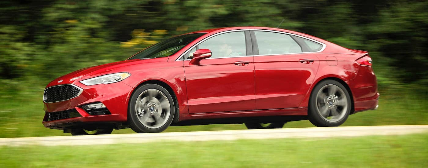 A red 2017 Ford Fusion is driving past grass and trees.