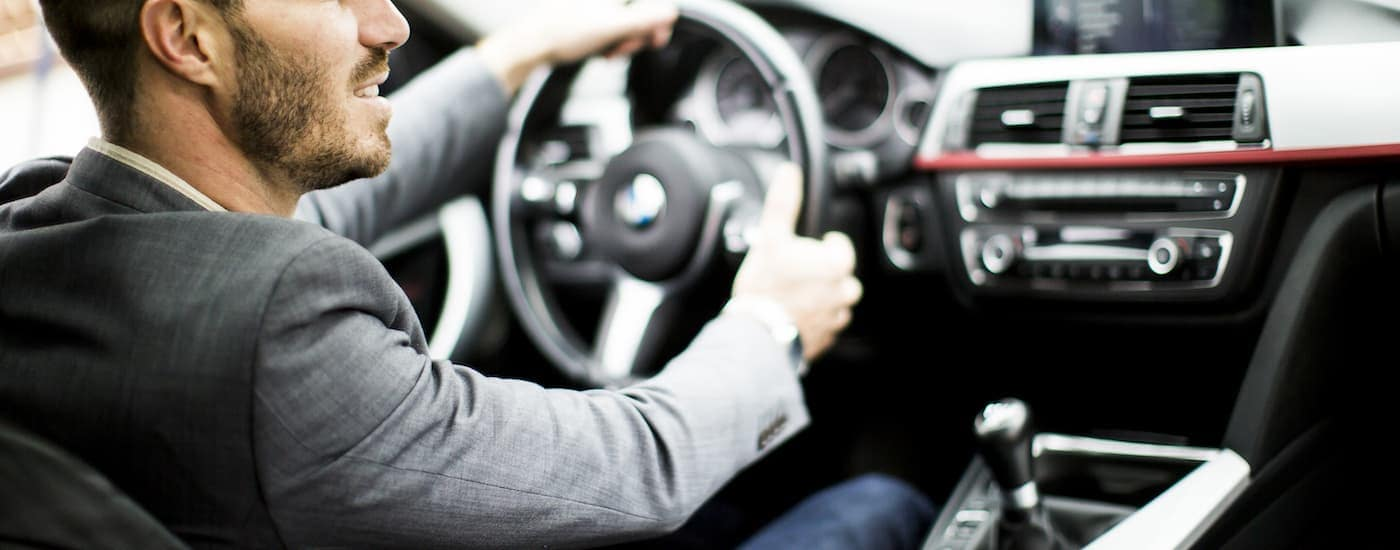 A man is shown test driving a car from the interior.