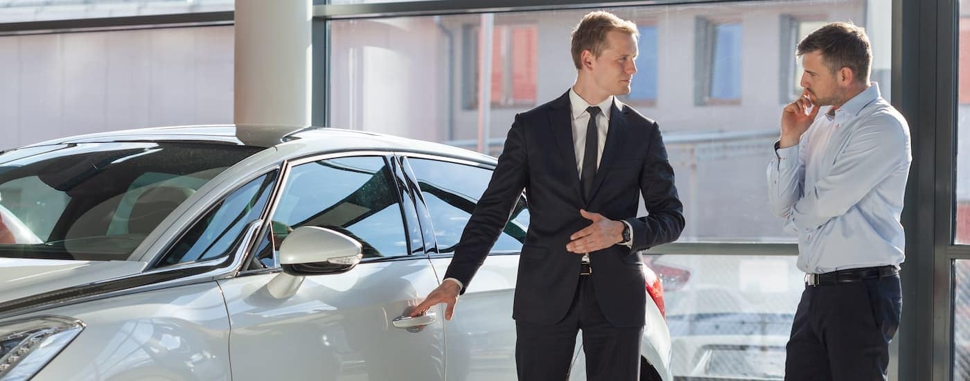 A salesman is showing a white used car for sale to a man in Milford, CT.