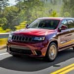 A red 2018 Jeep grand Cherokee is driving on a winding highway past trees near Milford, CT.