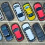 Two rows of cars are shown from a high angle at a Milford car dealer.