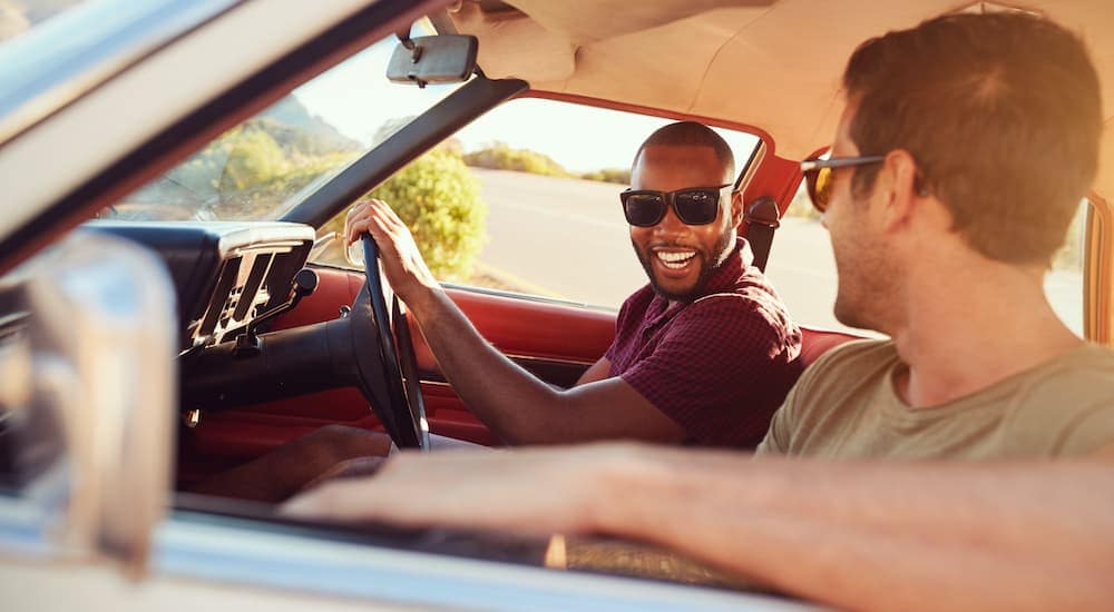 A close up shows two friends laughing through the passenger window of a car.