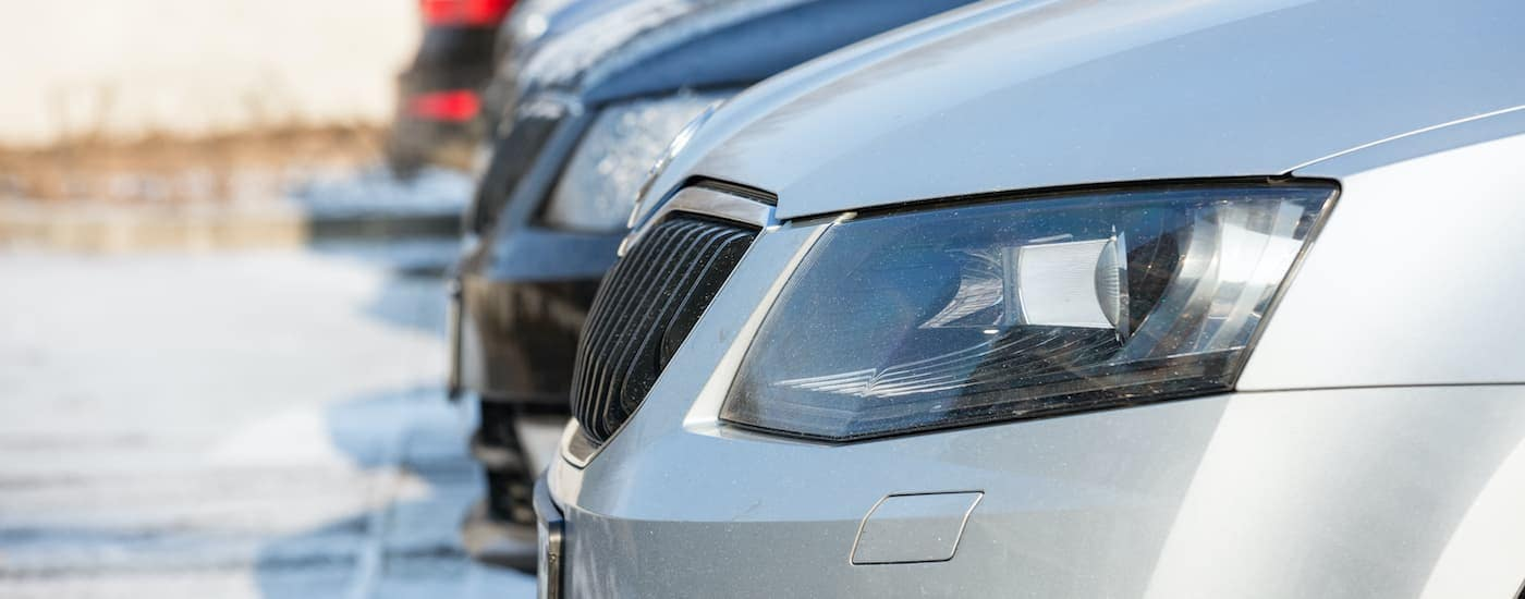 A close up shows a row of used cars at a Milford car dealer.