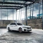 A white 2020 BMW 5 Series is shown parked in an empty warehouse.
