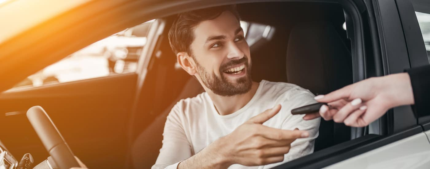 A close up shows a man sitting in a car while being handed a set of car keys.