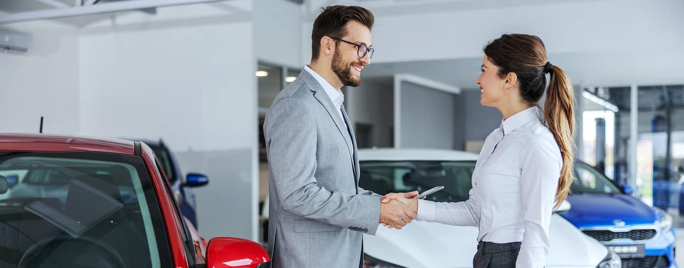 A close up shows to sales people talking in a dealership.
