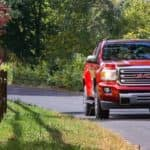 A red 2018 GMC Canyon SLT is shown from the front driving past a fence.