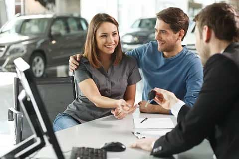 Smiling woman taking car keys from Nissan salesperson