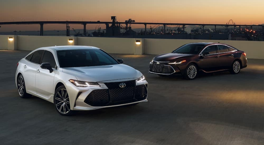 A silver 2020 Toyota Avalon is in front of a burgundy Avalon at sunset.