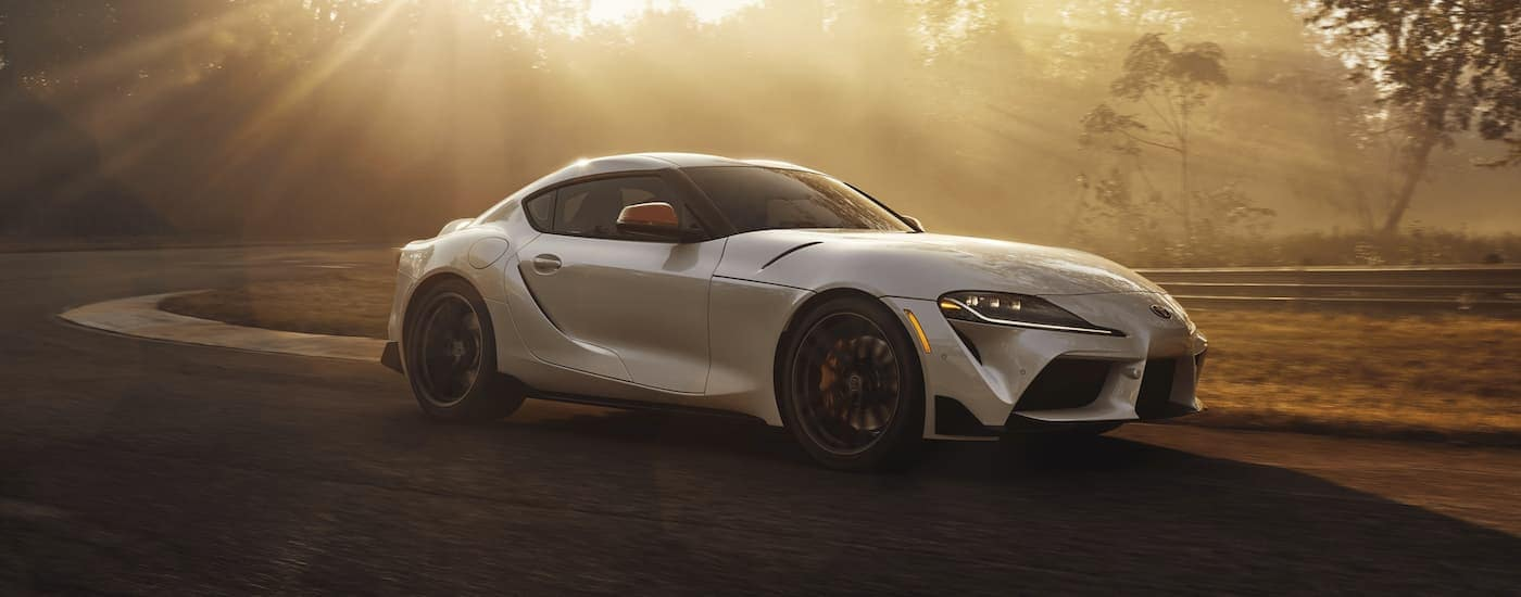 A silver 2020 Toyota GR Supra is driving around a race track with sun shining through the trees.