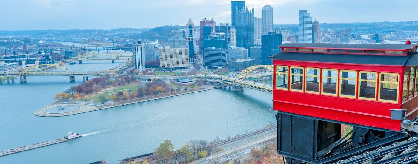 A red trolley is shown on the Duquesne Incline overlooking Pittsburgh, PA.