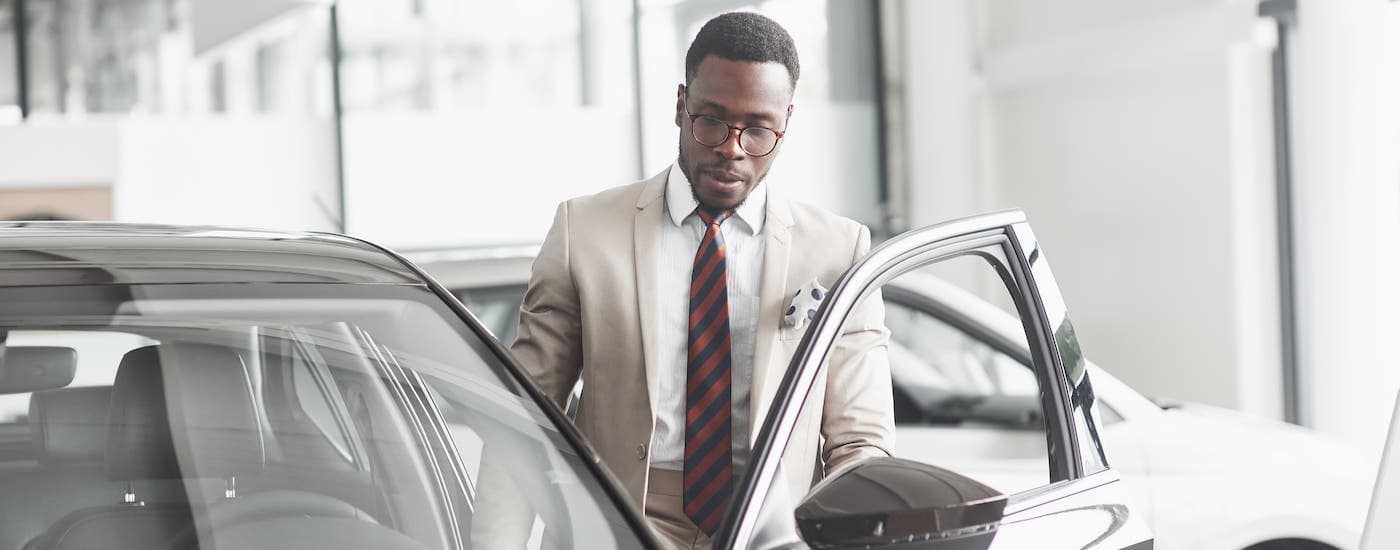A car salesman is inspecting a black car at a Toyota dealership near you.