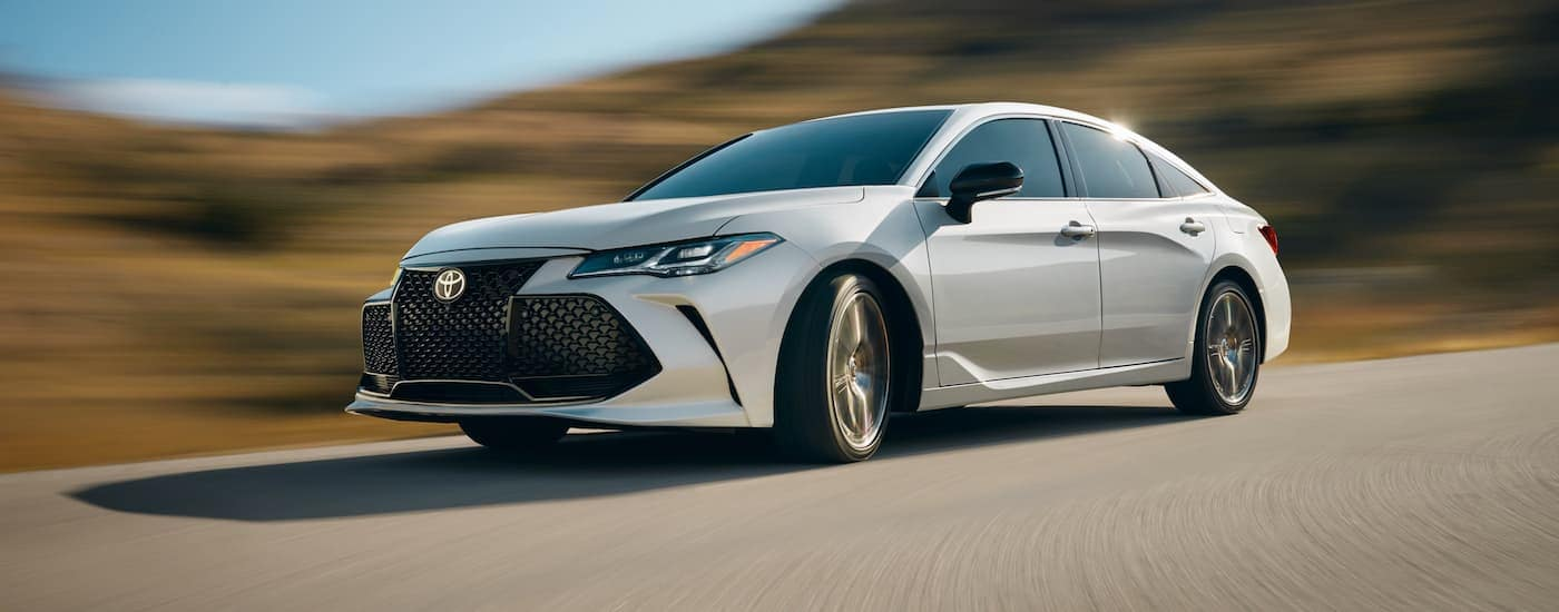 A white 2020 Toyota Avalon is driving around a corner past blurred hills.