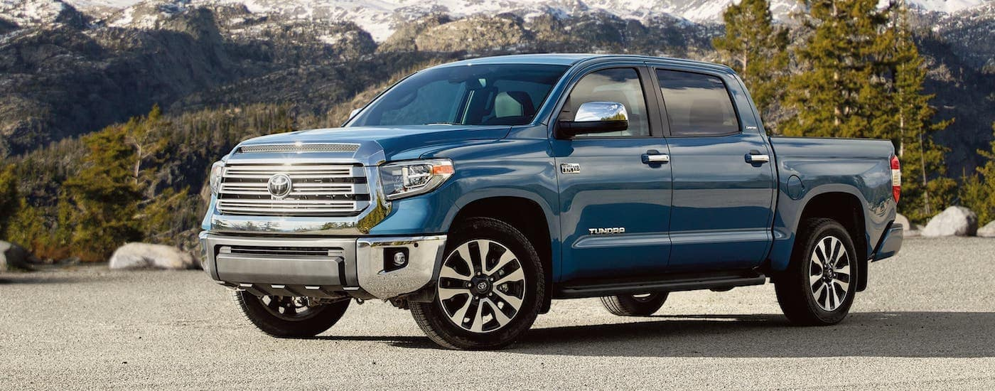 A blue Toyota Model, a 2020 Tundra Limited is parked in front of a forest.