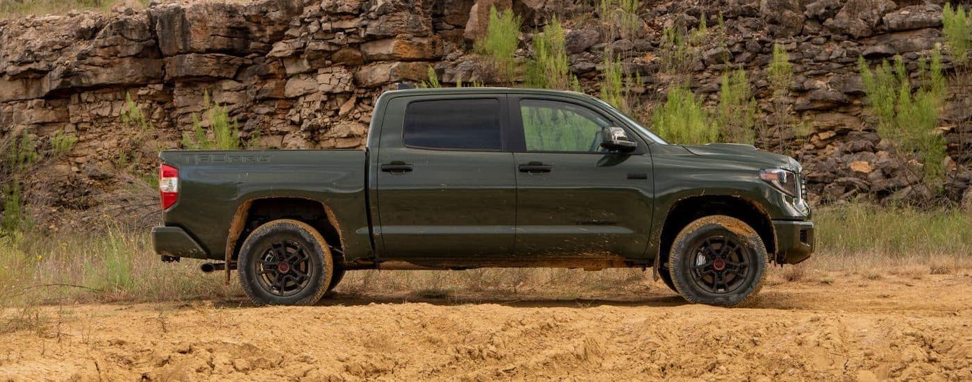 A mud-covered green 2020 Toyota Tundra TRD Pro is parked on a dirt trail.