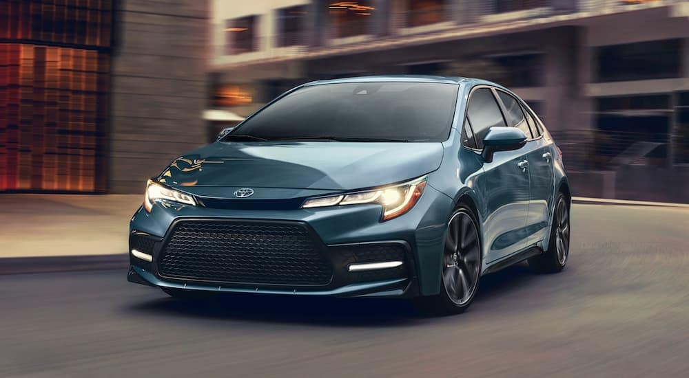 A blue 2020 Toyota Corolla is driving on a city street near Indiana, PA, after leaving a Toyota dealership near me.