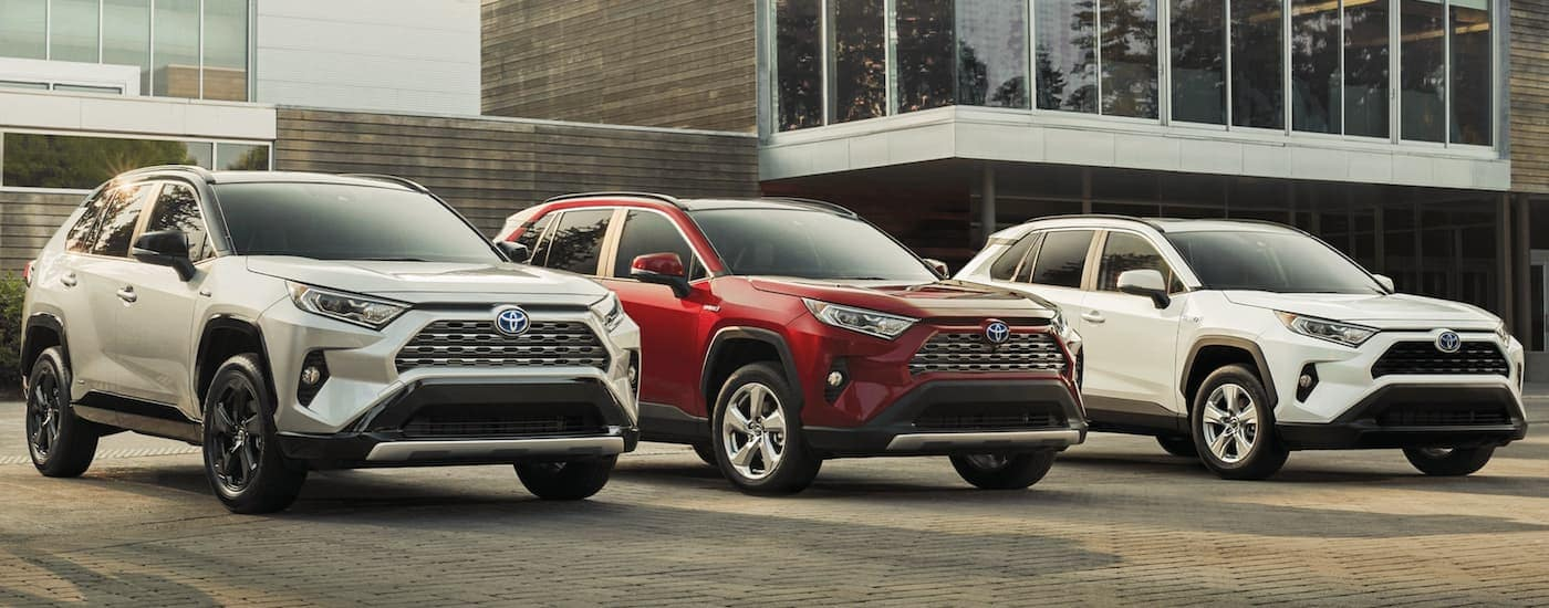 A silver, a red, and a white 2020 Toyota RAV4 are parked in front of a building.