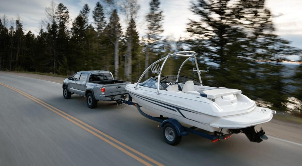 A grey 2020 Toyota Tacoma is towing a boat.