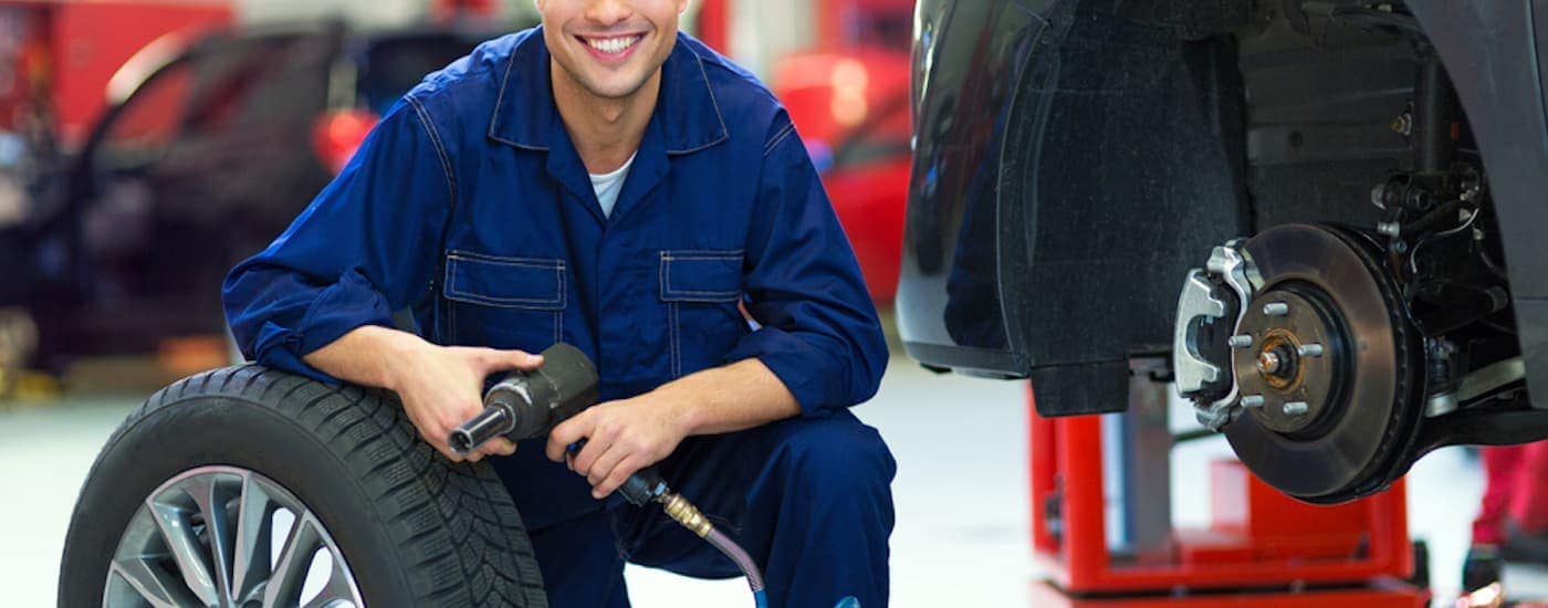 A mechanic is kneeling next to a car after removing a wheel.