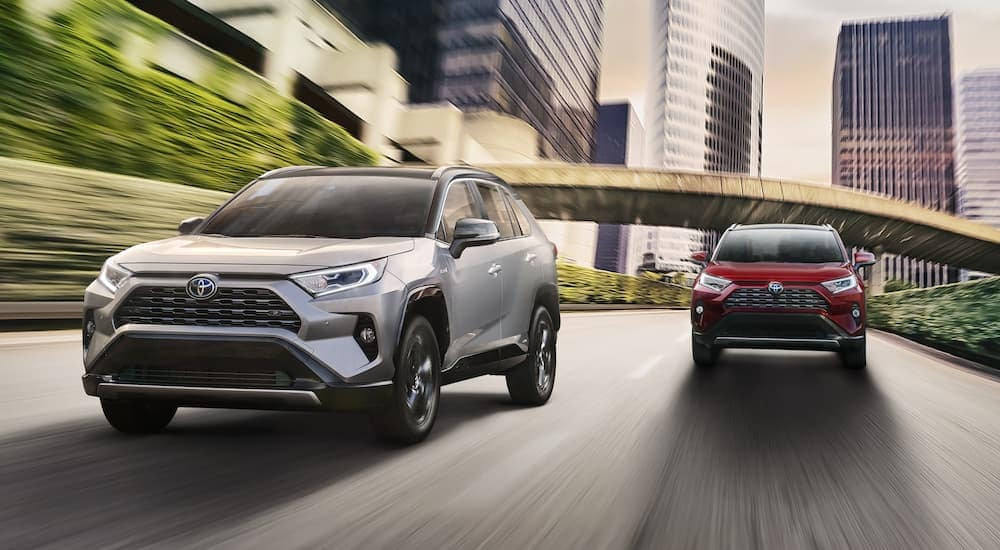 A silver 2020 RAV4 is driving in front of a red one on a city street.