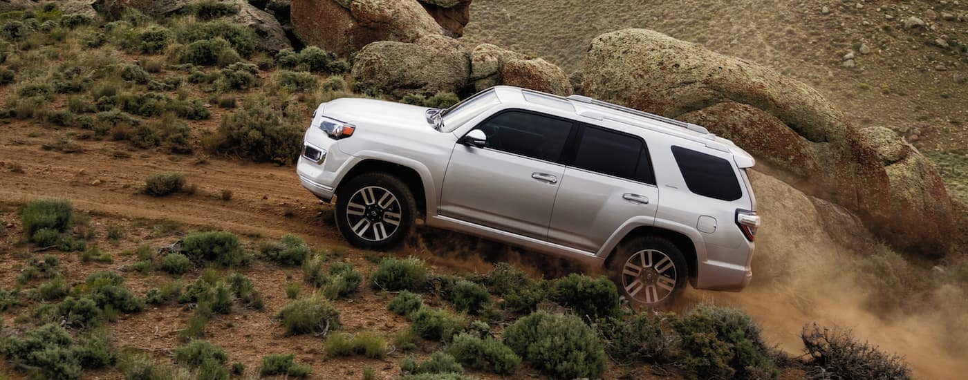 A white 2020 Toyota 4Runner is off-roading on a trail.