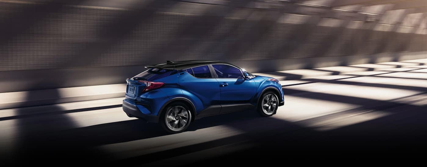 A blue 2020 Toyota C-HR is driving out of a tunnel.