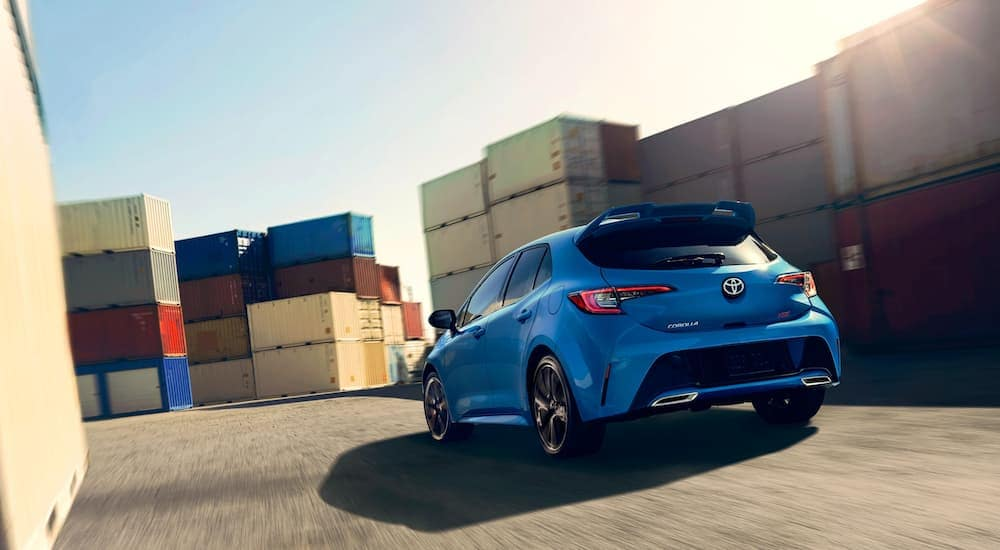 A blue 2020 Toyota Corolla Hatchback is driving through a shipping container storage area.