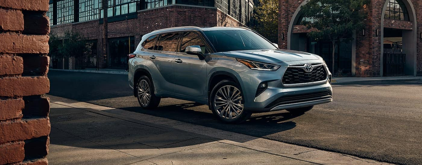 A blue 2020 Toyota Highlander is parked next to brick buildings.