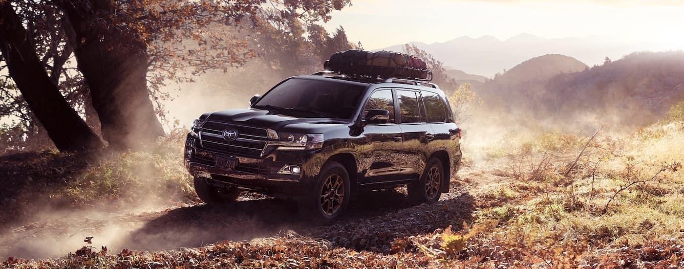 A black 2020 Toyota Land Cruiser, which is a recent Toyota model remake, is off-roading on a dusty trail.
