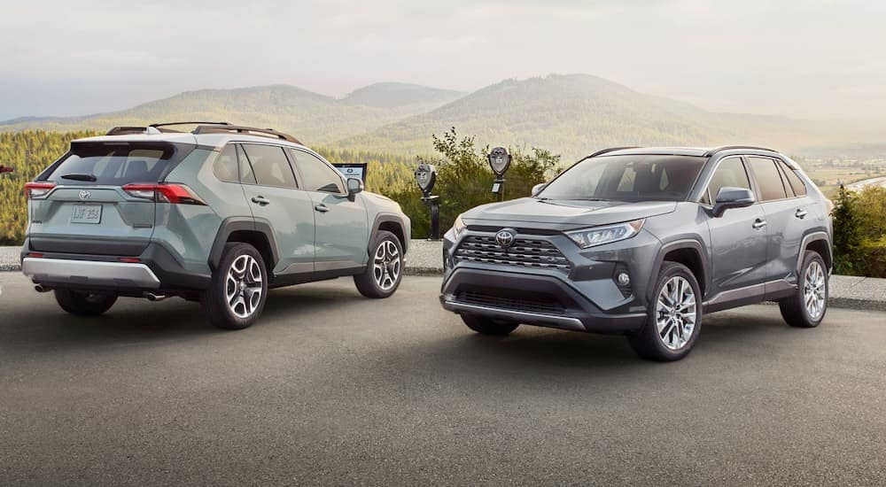 A light blue 2020 Toyota RAV4 is parked next to a silver one with a view of hills.