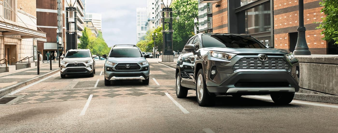 Three 2020 Toyota RAV4s, which are popular among Toyota models, are driving down a multi-lane city street.