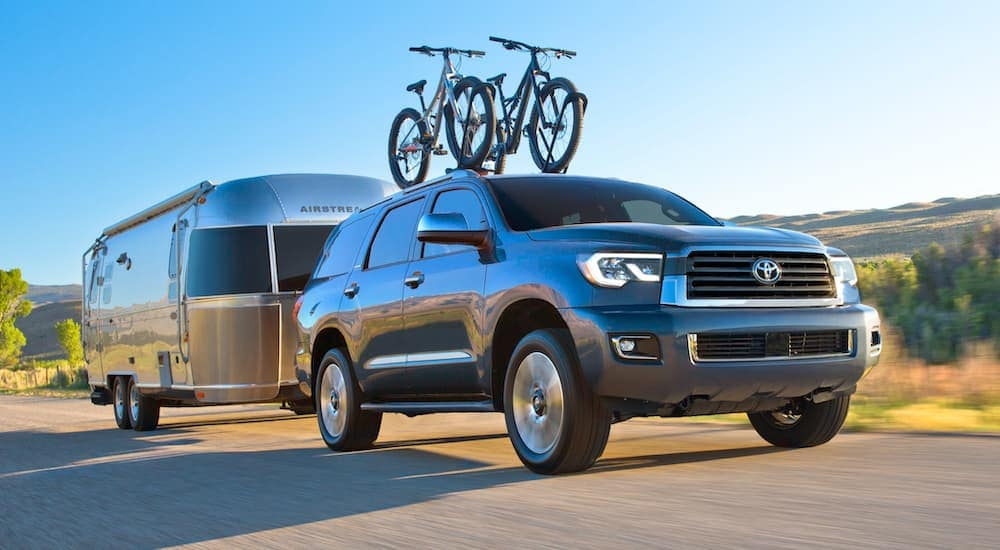 A dark grey 2020 Toyota Sequoia is towing an Airstream with bikes on its roof.