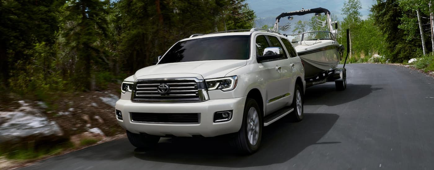 A white 2020 Toyota Sequoia is towing a boat.