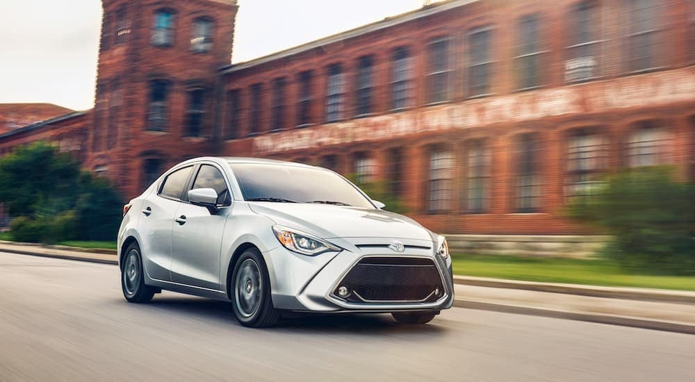 A silver 2020 Toyota Yaris is driving in front of a brick building near Indiana, PA.