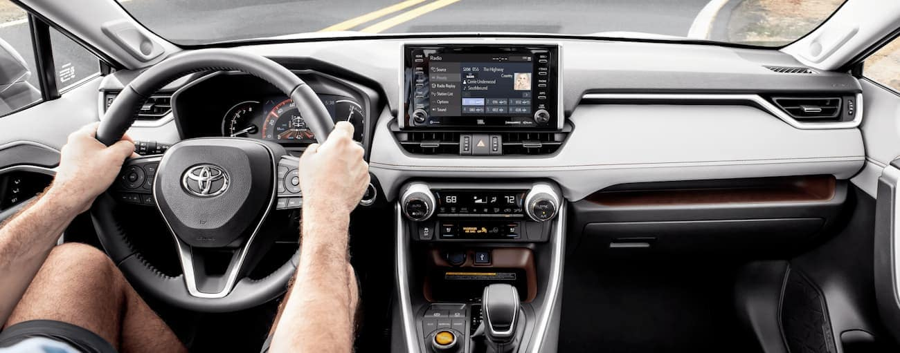 An interior view of a man driving a 2020 Toyota RAV4 is shown.