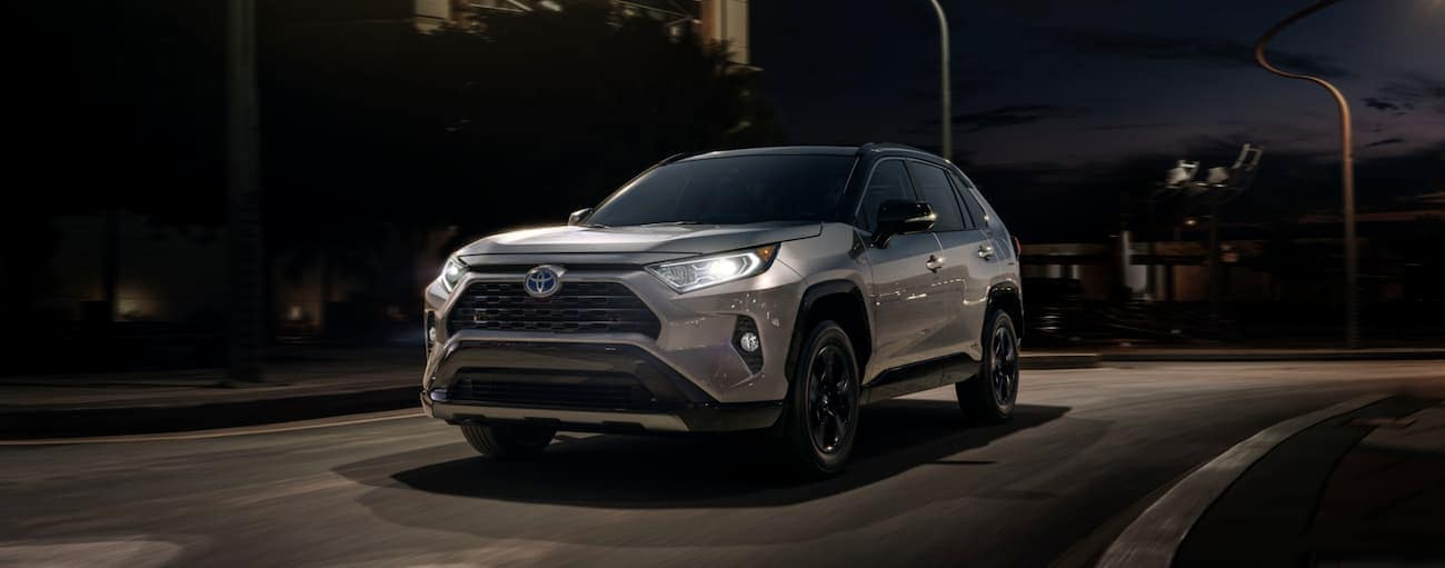 A silver and black 2020 RAV4 is parked on a city street at night.