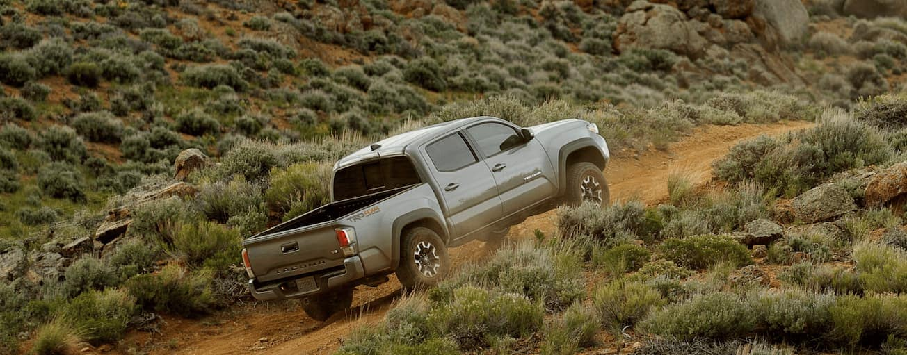 A grey 2020 Toyota Tacoma TRD is off-roading up a dirt trail.