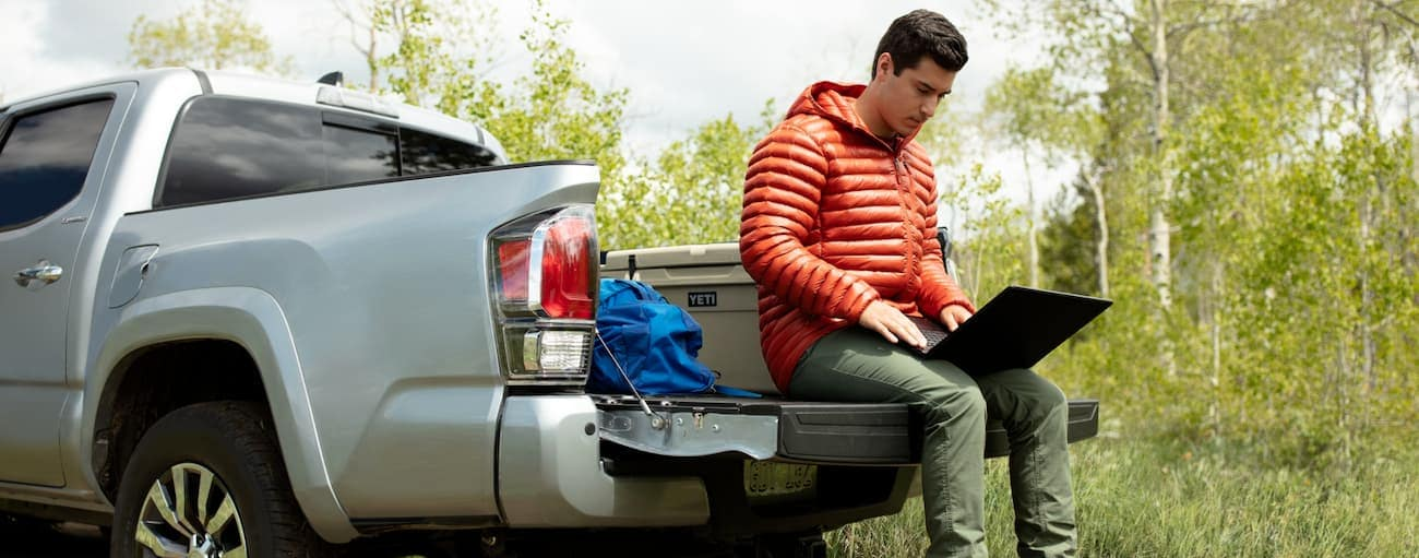 A man in an orange jacket is sitting on the tailgate of his silver 2020 Toyota Tacoma using a laptop near Indiana, PA.