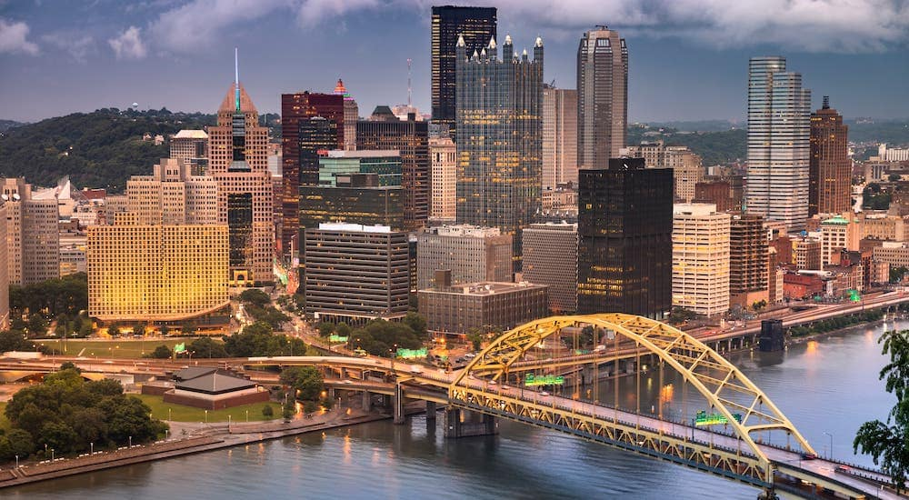 An aerial view is shown of the Fort Pitt bridge and the Pittsburgh, PA, skyline at dusk.