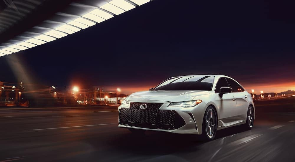 A white 2020 Toyota Avalon is driving on a highway near Indiana, PA, at night after leaving a Toyota dealership near me.