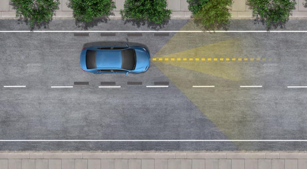 A diagram shows a blue car using the Lane Tracing Assist feature on a multi-lane road.