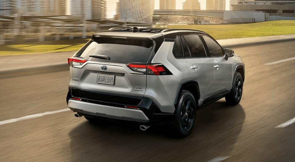 A silver 2020 Toyota RAV4 Hybrid is driving toward a city after leaving a Toyota dealership near me.