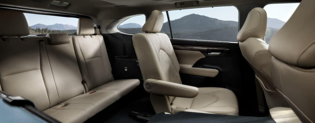 The cream interior of a 2020 Toyota Highlander Hybrid is shown from the side.