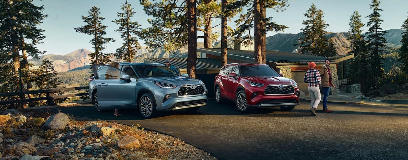 A blue and a red 2020 Toyota Highlander are parked in front of a mountain cabin.