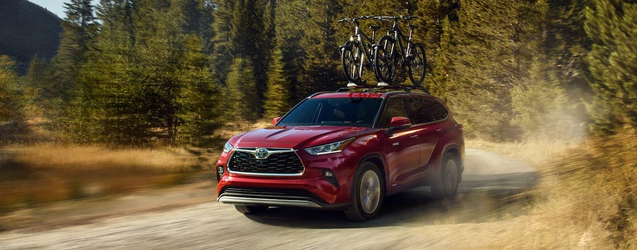 A red 2020 Toyota Highlander is driving on a dirt road with bikes on the roof near Indiana, PA.