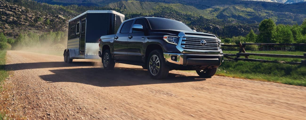 A black 2020 Toyota Tundra is towing an enclosed trailer on a dirt road.