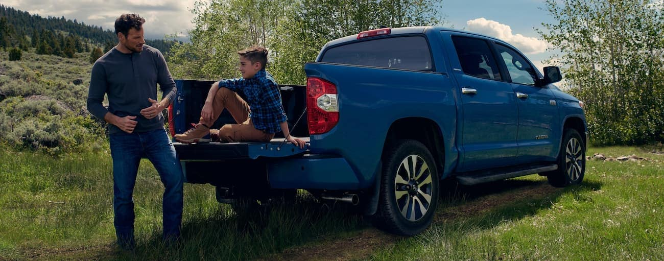 A boy is sitting on the tailgate of a blue 2020 Toyota Tundra while talking to his father in the grass.