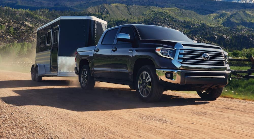 A black 2020 Toyota Tundra is towing a black enclosed trailer on a dirt road.